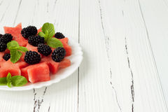 Refreshing watermelon salad with blackberries and mint. Fresh star shaped watermelon. Copy space background Royalty Free Stock Photo