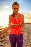 Healthy woman on beach with headphones listening to music Royalty Free Stock Photo