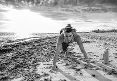 Active sportswoman in sports gear on beach workout Stock Photos