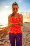 Fit sportswoman on seacoast with headphones listening to music Royalty Free Stock Photos