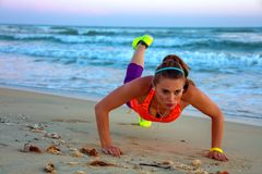 Fit woman in sport clothes on seashore at sunset doing pushups Royalty Free Stock Photography