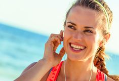 Happy fit woman on seacoast with headphones listening to music. Refreshing wild sea side workout. happy healthy fit woman in sportswear on the seacoast with Royalty Free Stock Image