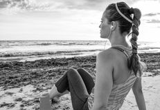 Pensive young fit woman on seashore relaxing after workout Royalty Free Stock Photos