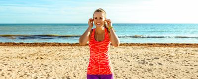 Sportswoman on seacoast with headphones listening to music. Refreshing wild sea side workout. smiling active sportswoman in sportswear on the seacoast with Royalty Free Stock Photo