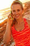 Smiling active woman on beach speaking on cell phone. Refreshing wild sea side workout. smiling active woman in sportswear on the beach speaking on a cell phone Stock Photo