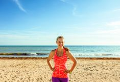 Smiling healthy fitness woman on beach looking into distance Stock Images