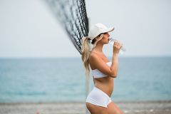 Refreshing after workout. Beautiful young blonde woman in sports clothing drinking water.  stock image