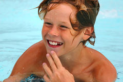 Refreshment. Smiling boy in a swimming pool Royalty Free Stock Images