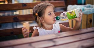 Refreshment is good on the summer days. Little girl sitting and eating ice cream. Space for copy. Close up royalty free stock photos