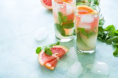 Refreshment grapefruit cocktail with mint. On mint color background. Healthy citrus summer drink Royalty Free Stock Photography