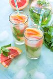 Refreshment grapefruit cocktail with mint. On mint color background. Healthy citrus summer drink Royalty Free Stock Photos