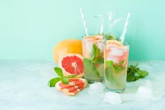 Refreshment grapefruit cocktail with mint. On mint color background. Healthy citrus summer drink Stock Photography