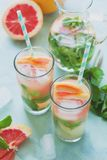 Refreshment grapefruit cocktail with mint. On mint color background. Healthy citrus summer drink. Toned Royalty Free Stock Images