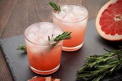 Refreshment grapefruit cocktail with rosemary on slate board. Royalty Free Stock Images