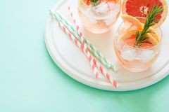 Refreshment grapefruit cocktail with rosemary on white wooden board Stock Photo