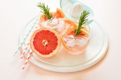 Refreshment grapefruit cocktail with rosemary on white wooden board Stock Image