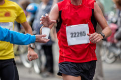 Refreshment. Hand of a volunteer giving a can of water at a refreshment point in a marathon race to an athlete, with the hand of the runner grabbing the water royalty free stock photography
