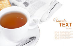 Refreshment with newspaper. A cup of tea and a newspaper with sample text on white Royalty Free Stock Images