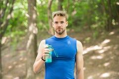 refreshment rafrescamento após o exercício do esporte do cervo o homem tem o rafrescamento com garrafa de água conceito do rafres imagens de stock royalty free