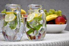 Refreshment or snack. Glass jugs with fresh water with mint and lemon and bowls full of tropical fruits on some garden party Royalty Free Stock Images