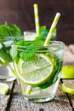 Refreshment time. Refreshment drink with lime,mint and ice in glass,selective focus Stock Image