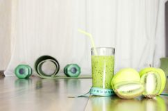 Closeup of measuring type, green smoothie and fruits on wooden floor.Concept of healthy, active nad sporty life. stock photography
