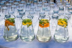 Refreshments Drinks Water Jugs. Refreshments drinks water lemon orange flavoured and glasses with serving jugs on table Stock Photography