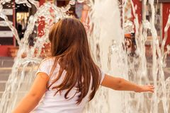 Refreshments by the fountain at summer hot day. Girl is refreshments by the fountain in the center of the city on a hot summer day stock photos