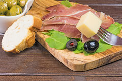 Refreshments of sliced Spanish ham and olives. Horizontally Stock Photos