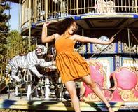 Refresque al adolescente real con el caramelo cerca de los carruseles en el PA de la diversión Foto de archivo libre de regalías
