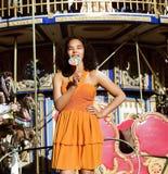 Refresque al adolescente real con el caramelo cerca de los carruseles en el PA de la diversión Fotografía de archivo