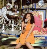 Refresque al adolescente real con el caramelo cerca de los carruseles en el parque de atracciones que camina, divirtiéndose Fotos de archivo libres de regalías