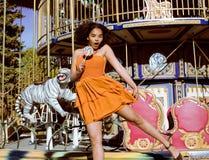 Refresque al adolescente real con el caramelo cerca de los carruseles en el parque de atracciones que camina, divirtiéndose Fotos de archivo