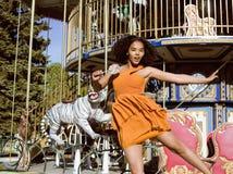 Refresque al adolescente real con el caramelo cerca de los carruseles en el parque de atracciones que camina, divirtiéndose Imagen de archivo