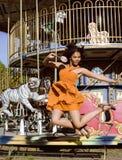 Refresque al adolescente real con el caramelo cerca de los carruseles en el parque de atracciones que camina, divirtiéndose Fotografía de archivo libre de regalías