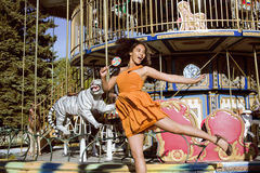 Refresque al adolescente real con el caramelo cerca de los carruseles en el parque de atracciones que camina, divirtiéndose Imagen de archivo libre de regalías