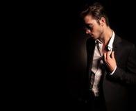 Refresque al hombre de la moda en el traje y las gafas de sol que tiran de su cuello Foto de archivo