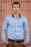 Refresque al hombre de la moda en la camisa azul que se coloca y que mira lejos Fotos de archivo libres de regalías