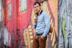 Refresque al hombre de la moda en la camisa azul que se coloca y que mira lejos Fotos de archivo