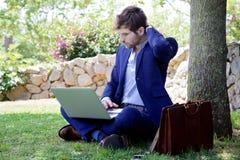 Refresque al hombre de negocios hermoso que trabaja en el ordenador portátil del cuaderno, en el parque verde Imagen de archivo