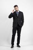 Refresque al hombre de negocios joven en el teléfono que mira lejos Imagen de archivo libre de regalías
