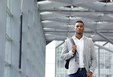 Refresque al hombre joven que camina dentro del edificio de la estación con el bolso Imágenes de archivo libres de regalías