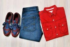 Refresque el equipo casual del ` s de los hombres de la moda en el fondo de madera, pantalones de los tejanos, zapatilla de depor Imagenes de archivo