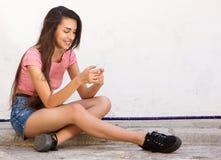 Refresque el exterior que se sienta de la muchacha adolescente que mecanografía en el teléfono celular Imagen de archivo