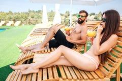 Refresque la imagen del hombre joven y de la mujer que se sientan en sunbeds La muchacha bebe el cóctel y la mirada directos El i fotografía de archivo libre de regalías