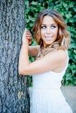 Refresque a la mujer bonita que se inclina en un tronco de árbol Imagenes de archivo