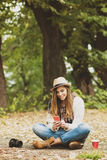Refresque a la mujer joven que usa smartphone en parque en otoño Fotos de archivo libres de regalías