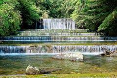 Refresque las cascadas de restauración que caen abajo de la corriente en un bosque misterioso del verdor enorme Imagenes de archivo