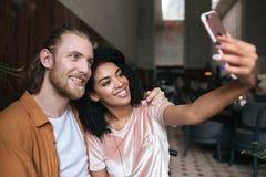 Refresque los pares jovenes que hacen las fotos en cámara frontal del teléfono móvil en restaurante Señora afroamericana bonita q imagen de archivo libre de regalías