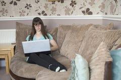 Refrigeración en el sofá usando un ordenador portátil fotografía de archivo libre de regalías